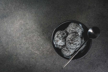 Alimento d'avanguardia. Gelato nero con sesamo nero, in una ciotola nera su un tavolo in pietra nera, con un cucchiaio. Copia spazio vista superiore