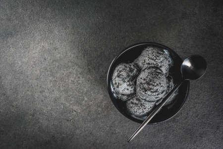 Trendy food. Zwart ijsje met zwarte sesam, in een zwarte kom op een zwarte stenen tafel, met een lepel. Kopieer de bovenaanzicht van de ruimte