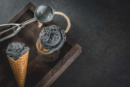 Trendy food. Black ice cream with black sesame, in traditional portioned ice cream cones. On a black stone table, in a wooden tray. Copy space Zdjęcie Seryjne