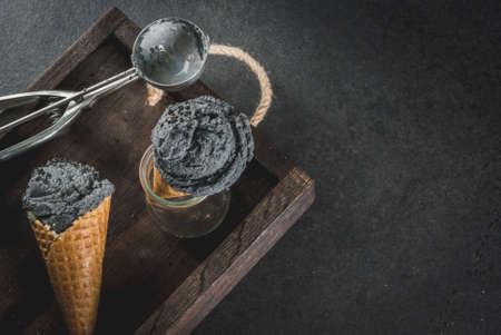 Trendy food. Zwart ijsje met zwarte sesam, in traditionele porties ijsjes. Op een zwarte stenen tafel, in een houten bakje. Kopieer de ruimte Stockfoto