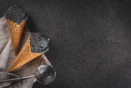 Alimento di tendenza. Gelato nero con sesamo nero, in coni tradizionali congelati di gelato. Su un tavolo in pietra nera, in un vassoio di legno. Copia spazio vista superiore