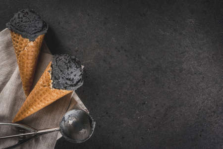 Trendy food. Black ice cream with black sesame, in traditional portioned ice cream cones. On a black stone table, in a wooden tray. Copy space top view Zdjęcie Seryjne