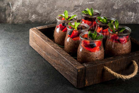 Healthy vegan breakfast. Dessert. Alternative food. Pudding with chia seeds, fresh strawberries, blackberries and mint. On a dark stone background, in an old wooden tray. Copy space