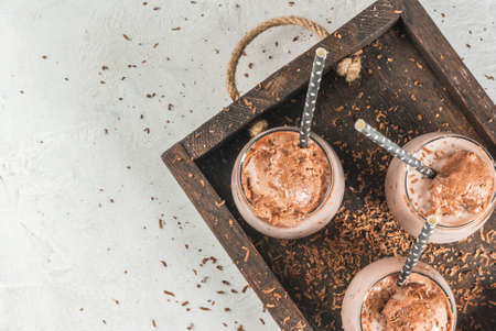 Bebidas refrescantes de verano Cacao helado de chocolate helado. Con una bola de helado de chocolate, chocolate en polvo y hielo. En gafas, con tubos. Bandeja de madera de mesa de hormigón blanco. Copia espacio vista superior Foto de archivo - 79388430