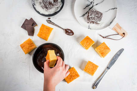 Australian cuisine. Preparation of traditional Australian dessert Lamington: biscuit in chocolate with coconut shaving powder. Top view, female hands in the frame. On a white table. The girl dips biscuit into chocolate Stock Photo