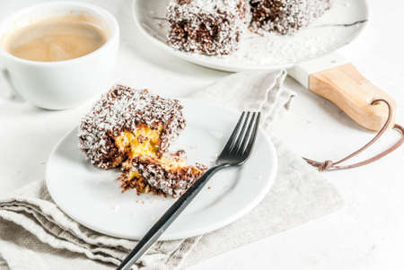Australian food. Traditional dessert Lamington - pieces of biscuit in dark chocolate, sprinkled with coconut powder chips. On a marble plate, white table. With coffee mug. Copy space
