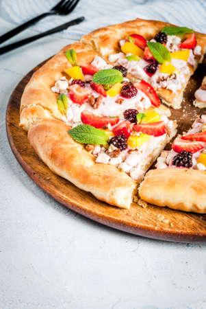 Zomerse snacks. Eten voor feest. Fruitpizza met room, krenten, yoghurt, aardbeien, mango, perziken, bananen, bramen, chocolade, walnoten, munt. Op lichtblauwe tafel. Ruimte kopiëren Stockfoto