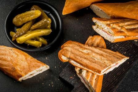 Cubaans traditioneel voedsel, snack, partijvoedsel. Cubaanse sandwich van baguette met ham, varkensvlees, kaas, groenten in het zuur. Op zwarte tafel kopie ruimte