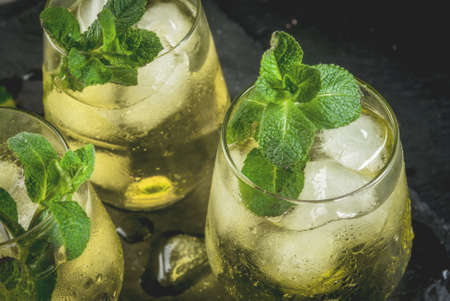 Traditional Spanish alcoholic drink, Rebujito cocktail - white wine, carbonated water (soda), mint, lemon juice. On a black slate board close view