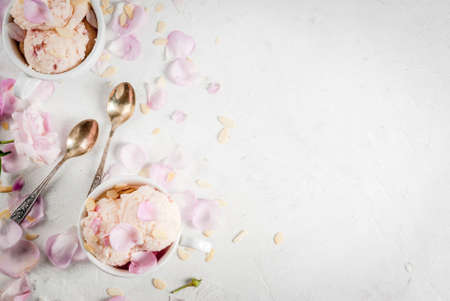 Summer refreshing desserts. Vegan diet food. Ice cream with rose petals and slices of almond, in white serving bowls, on a white concrete table. Copy space top view Stock Photo