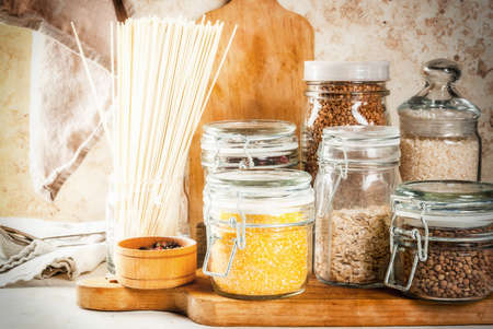 Selection of gluten-free products, cereals: xanthan gum. buckwheat,Rice, rice noodles, chickpeas, lentils, corn, beans, oatmeal. In the home kitchen, in jars. Copy space Stok Fotoğraf