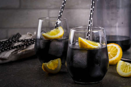 Trendy food. Summer refreshment drinks. Detox and diet concept. Black lemonade with charcoal, ice, lemon juice and lemon. On a home stone table, with black straws for drinking. Copy space Stock fotó - 79922585