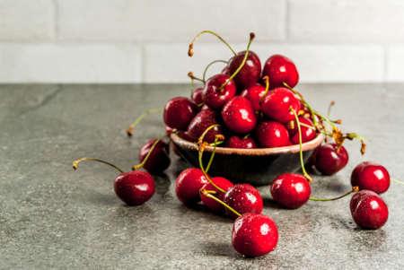Frutas sazonais orgânicas crus frescas. Cereja com gotas de água sobre uma mesa de pedra escura. Espaço da cópia Foto de archivo - 80022599