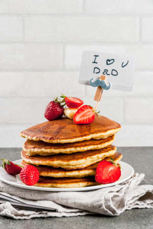 Celebrating Fathers Day. Breakfast. The idea for hearty and delicious holiday breakfast: pancakes with butter, maple syrup and fresh strawberries, with congratulations. Coffee cup. Copy space