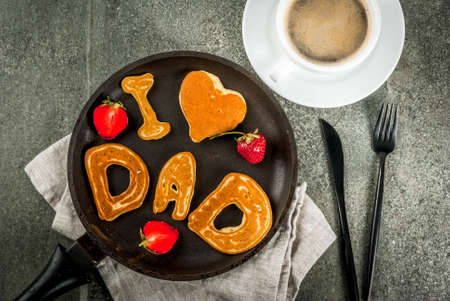 Celebrating Fathers Day. Breakfast. The idea for a hearty and delicious breakfast: pancakes in form of congratulations - I love dad. In a frying pan, coffee mug and strawberries. Top view copy space