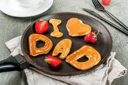 Celebrating Father's Day. Breakfast. The idea for a hearty and delicious breakfast: pancakes in form of congratulations - I love dad. In a frying pan, coffee mug and strawberries. copy space 스톡 콘텐츠