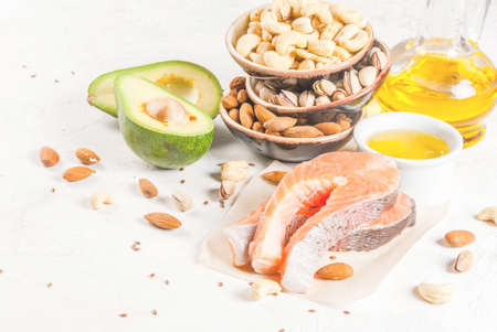 Healthy food. Products with healthy fats. Omega 3, omega 6. Ingredients and products: trout (salmon), flaxseed oil, avocado, almonds, cashews, pistachios. On a white stone table. Copy space Stock Photo