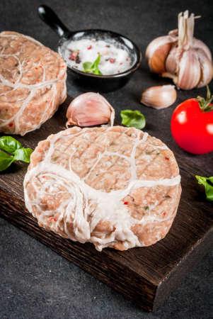 Viande organique crue. Escalopes de poulet aux hamburgers, avec une grille de porc, pour griller ou frire. Avec des épices, du basilic, des tomates, sur une table en pierre grise sur une planche de bois coupante. Copier l'espace Banque d'images - 80150865