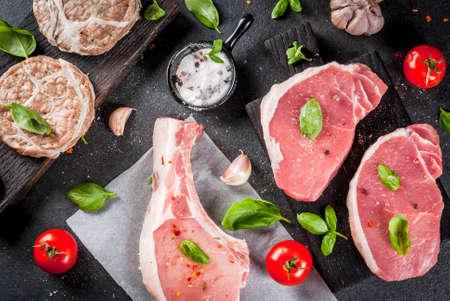 Viande organique crue. Sélection de plusieurs types de viandes rouges: côtelette de porc sur os, steaks de porc et côtelettes de poulet en grille de graisse de porc. Avec des ingrédients pour cuisiner, vue de dessus de table en pierre grise Banque d'images - 80170968