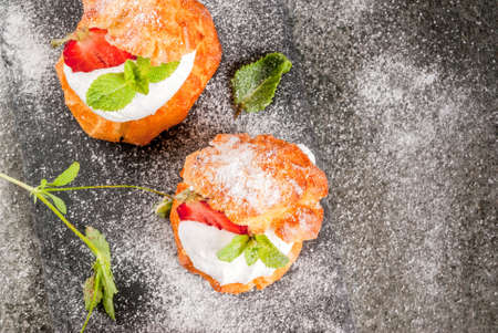 sprinkling: Summer desserts. Homemade baking. Cake profiteroles with whipped cream, fresh strawberries, mint and sprinkling of powdered sugar. On a black stone table. Copy space top view Stock Photo