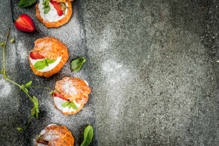 Summer desserts. Homemade baking. Cake profiteroles with whipped cream, fresh strawberries, mint and sprinkling of powdered sugar. On a black stone table. Copy space top view Stock Photo