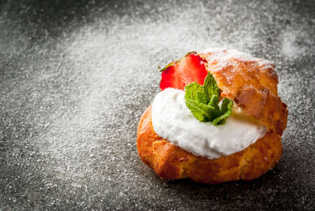 Summer desserts. Homemade baking. Cake profiteroles with whipped cream, fresh strawberries, mint and sprinkling of powdered sugar. On a black stone table. Copy space