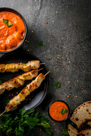 Indian food. Traditional dish spicy chicken tikka masala, butter chicken curry, with indian naan butter bread, spices, herbs. Served in bowl. sauce, on skewers. Stone dark table. copy space top view Stock Photo