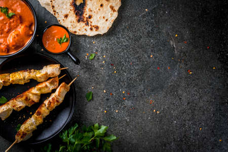 Indian food. Traditional dish spicy chicken tikka masala, butter chicken curry, with indian naan butter bread, spices, herbs. Served in bowl. sauce, on skewers. Stone dark table. copy space top view Stok Fotoğraf
