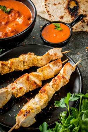 Indian food. Traditional dish spicy chicken tikka masala, butter chicken curry, with indian naan butter bread, spices, herbs. Served in bowl. Sauce, on skewers. Stone dark table. Copy space Stock Photo