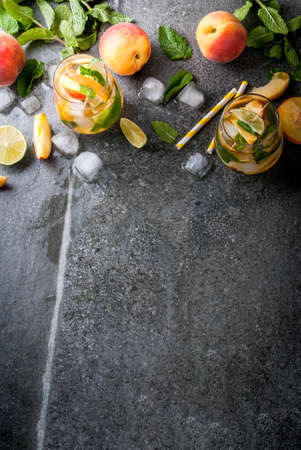 Summer refreshment drinks. Peach mojito with lime, peach and mint. With the ingredients on a dark stone table.  copy space top view