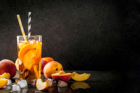 Summer refreshment drinks. Iced tea with pieces of organic home-made peach of nectarine. On a black stone background, with ice and ingredients. Copy space Stock Photo