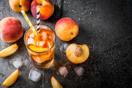 Summer refreshment drinks. Iced tea with pieces of organic home-made peach of nectarine. On a black stone background, with ice and ingredients. Copy space top view