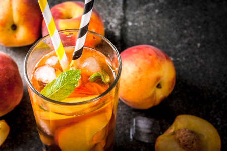 Summer refreshment drinks. Iced tea with pieces of organic home-made peach of nectarine. On a black stone background, with ice and ingredients. Copy space close view