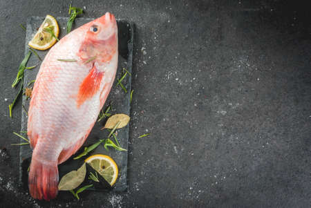 Raw fish red tilapia on a chopping board on a black stone table, with spices, lemon and herbs for cooking. Top view copy space Banco de Imagens - 80380403