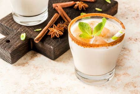 Traditional Indian drink is iced tea or chai masala, with ice cubes from chai, milk and mint leaves. With striped straws, on a wooden board. On light beige stone table. Copy space