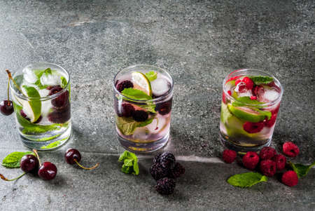 Set of traditional summer refreshing drinks berry mojito. With lime, mint leaves, blackberries, raspberries and cherries. With the ingredients on a dark stone table. Copy space Stock Photo
