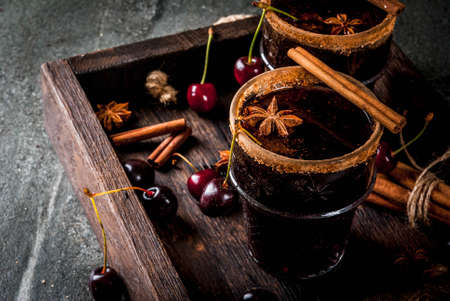 Autumn and winter drinks. Hot cherry  sangria with cinnamon, anise, wine and spices. On a stone dark and wooden background with ingredients, Copy space, in tray Stock Photo