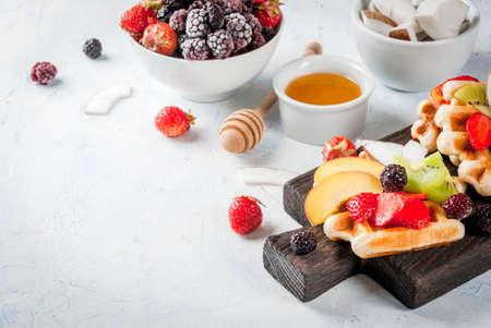 Breakfast. Homemade fresh Belgian soft wafers with honey, fruits, nuts, berries - peach, blackberries, raspberries, strawberries, coconut, cashews, strawberries, mint. Light table. Copy space
