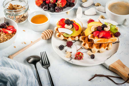 Breakfast. Home-made fresh Belgian soft wafers with honey, fresh fruits, nuts and berries; Yoghurt with granola and fruit, a cup of coffee. Light concrete table. Copy space   Stock Photo