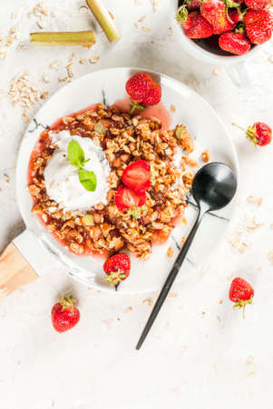 Healthy breakfast. Oatmeal granola crumble with rhubarb, fresh strawberries and blackberries, seeds and ice cream on marble white plate, with mint, on white stone concrete table, copy space top view