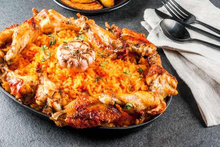 西アフリカの国の料理。グリルチキンのジョロフ ライスは、羽を広げ、揚げバナナ、バナナ。灰色の石テーブル。コピー スペース