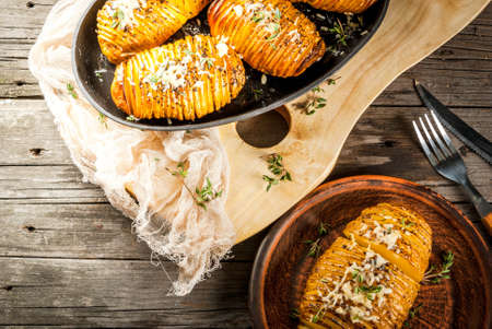 jacket potato: American traditional home cooking. The vegan diet. Homemade Hasselback Potato with Fresh Herbs and cheese. On old wooden table, copy space