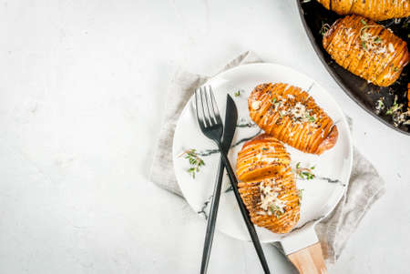 American traditional home cooking. The vegan diet. Homemade Hasselback Potato with Fresh Herbs and cheese. On white table, copy space top view Stock Photo