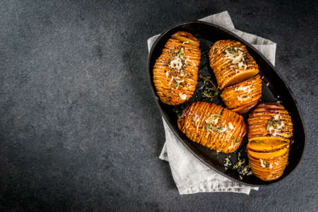 acordeon: American traditional home cooking. The vegan diet. Homemade Hasselback Potato with Fresh Herbs and cheese. On black table, copy space top view