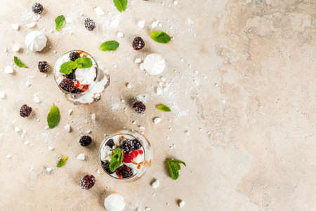 Traditional English dessert. Eton mess - whipped cream, meringue, fresh blackberries, sauce and caramel. In serving glasses on a light stone table. Copy space top view Stock Photo