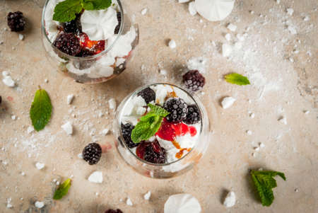 Traditional English dessert. Eton mess - whipped cream, meringue, fresh blackberries, sauce and caramel. In serving glasses on a light stone table. Copy space Stock Photo