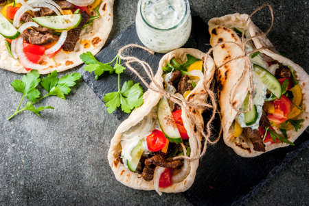 Healthy snack, lunch. Traditional Greek wrapped sandwich gyros - tortillas, bread pita with a filling of vegetables, beef meat and sauce tzatziki. Imagens