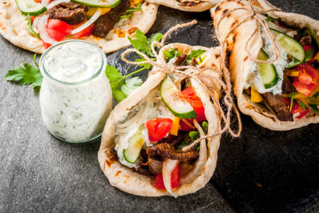 Healthy snack, lunch. Traditional Greek wrapped sandwich gyros - tortillas, bread pita with a filling of vegetables, beef meat and sauce tzatziki. Stock Photo