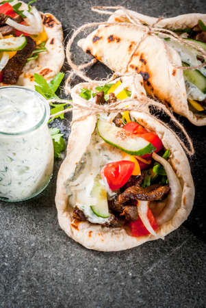 Healthy snack, lunch. Traditional Greek wrapped sandwich gyros - tortillas, bread pita with a filling of vegetables, beef meat and sauce tzatziki. 版權商用圖片