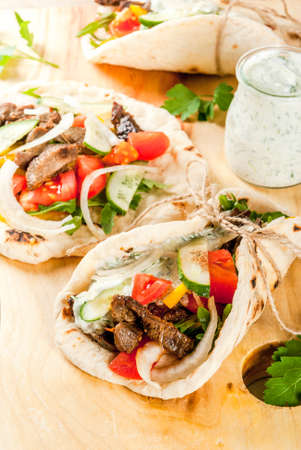 Merienda saludable, almuerzo. Giros tradicionales en sándwich envueltos en griego: tortillas, pan pita con relleno de verduras, carne de res y salsa tzatziki. Foto de archivo - 80933599